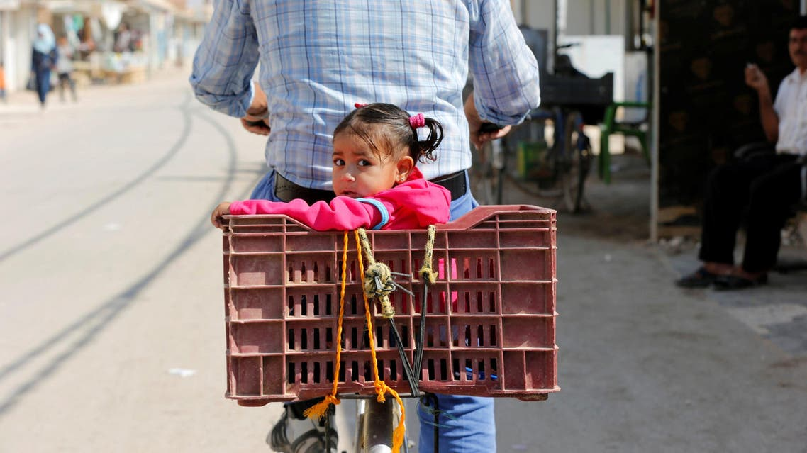 A Syrian refugee rides a bicycle with his daughter at the main market, in the Al-Zaatri refugee camp in the Jordanian city of Mafraq, Jordan, near the border with Syria September 17, 2016. REUTERS