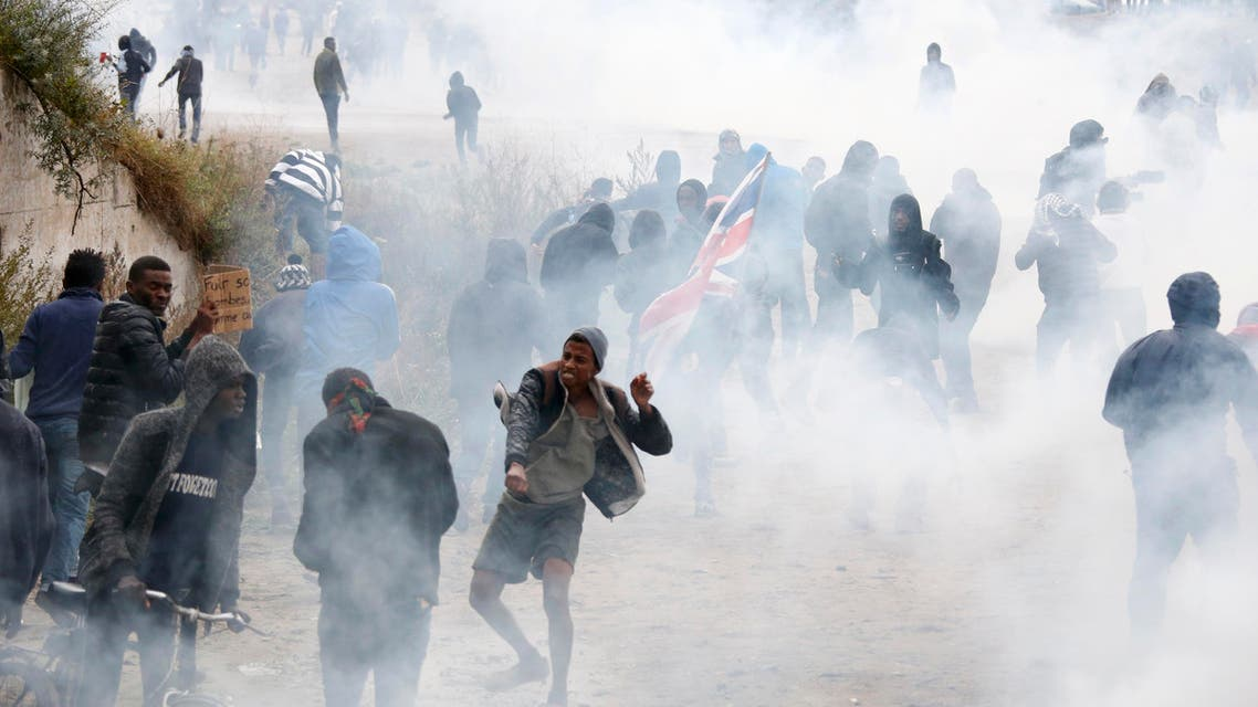 """Tear gas fills the air as French riot police face off with demonstrators near the area called the """"jungle"""" where migrants live in Calais, France, October 1, 2016. REUTERS"""