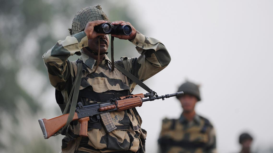 Qn Indian Border Security Force (BSF) soldier looks through a binocular towards Pakistan during a patrol at the India-Pakistan border in R.S Pora, southwest of Jammu, on October 3, 2016.