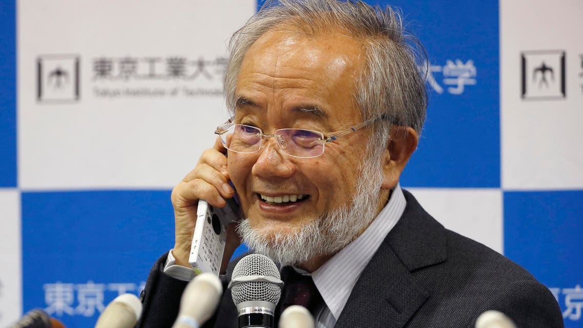 Nobel Prize winner Yoshinori Ohsumi smiles as he speaks with Japanese Prime Minister Shinzo Abe on a mobile phone during a press conference at the Tokyo Institute of Technology in Tokyo Monday, Oct. 3, 2016. AP