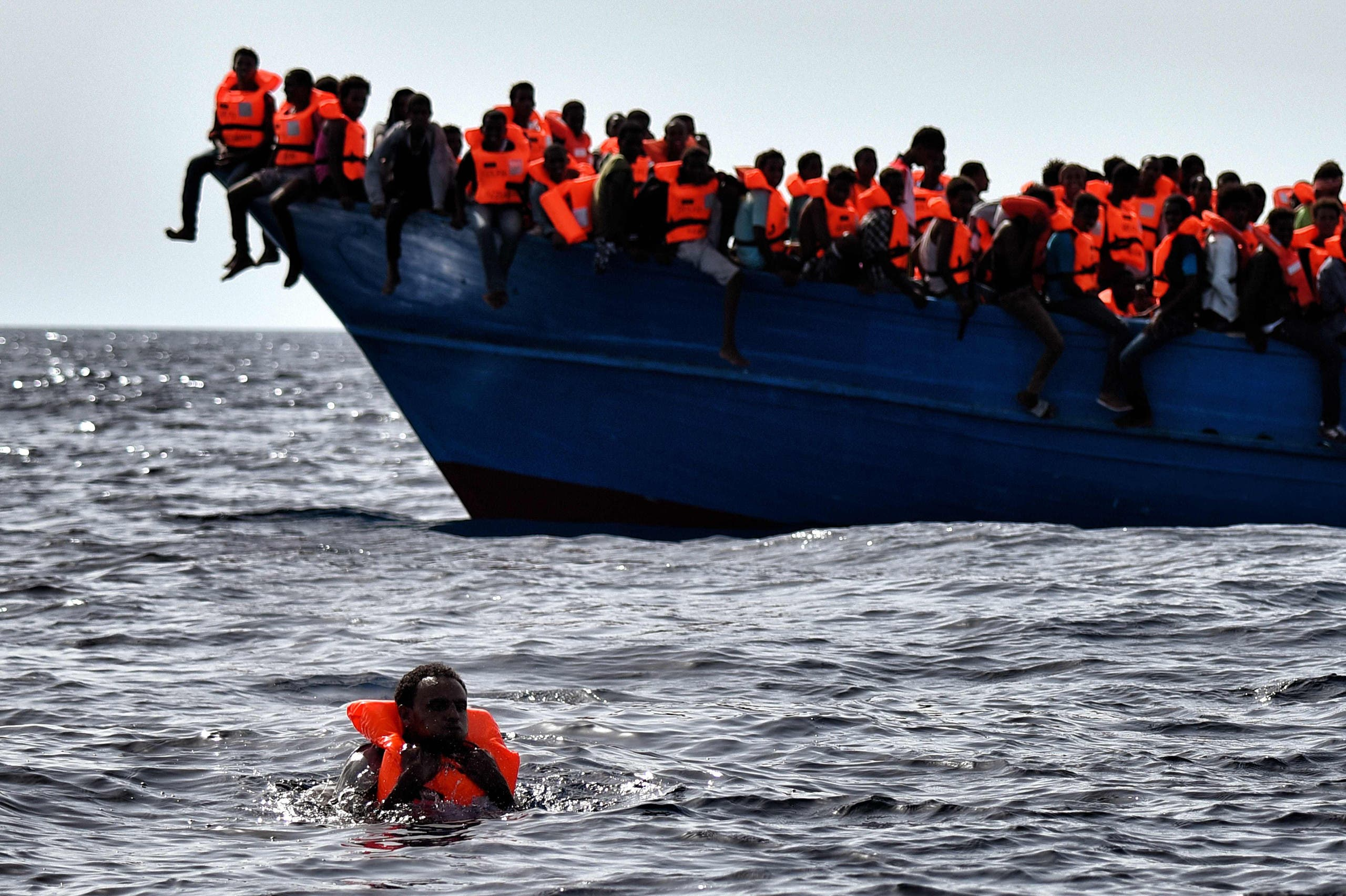 Migrants wait to be rescued as they drift in the Mediterranean Sea some 20 nautical miles north off the coast of Libya on October 3, 2016. Italy coordinated the rescue of more than 5,600 migrants off Libya, three years to the day after 366 people died in a sinking that first alerted the world to the Mediterranean migrant crisis. (AFP)