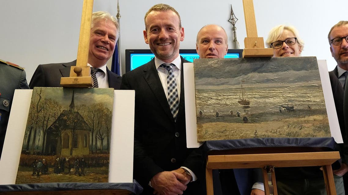 "AFP Axel Ruger (C), Director of the Van Gogh museum poses next to two recently recovered stolen paintings by late Dutch artist Vincent Van Gogh entitled ""Congregation Leaving the Reformed Church in Nuenen"" (L) and ""The Beach At Scheveningen During A Storm"" (R) in Naples on September 30, 2016."