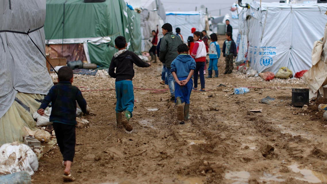 In this Monday, Jan. 4, 2016 file photo, Syrian refugee children walk in mud after a heavy rain at a refugee camp in the town of Hosh Hareem, Bekaa valley, east Lebanon. In a report published Tuesday, Jan. 12, 2016, the New York-based rights group Human Rights Watch said Lebanese residency laws are putting Syrian refugees in danger. The regulations, adopted a year ago, have forced refugees to either return to Syria, where they are at risk of persecution, torture or death, or to stay in Lebanon illegally, leaving them vulnerable to exploitation and abuse. (AP)