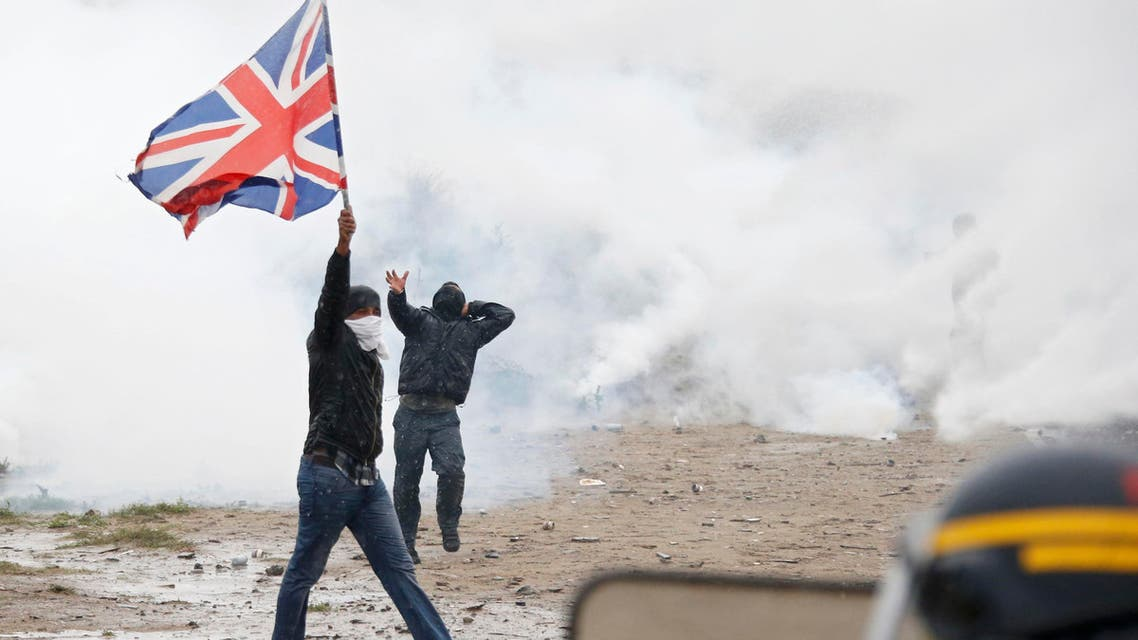 """Tear gas fills the air as French riot police face off with demonstrators near the area called the """"jungle"""" where migrants live in Calais, France, October 1, 2016. (Reuters)"""