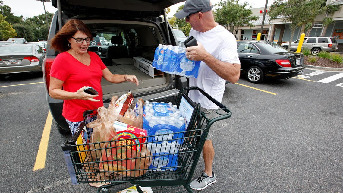 Laura and George Callahan of James Island, South Carolina, load up their vehicle with bottled water and food purchased ahead of the arrival of Hurricane Matthew, in Folly Beach, South Carolina, U.S. October 6, 2016. REUTERS
