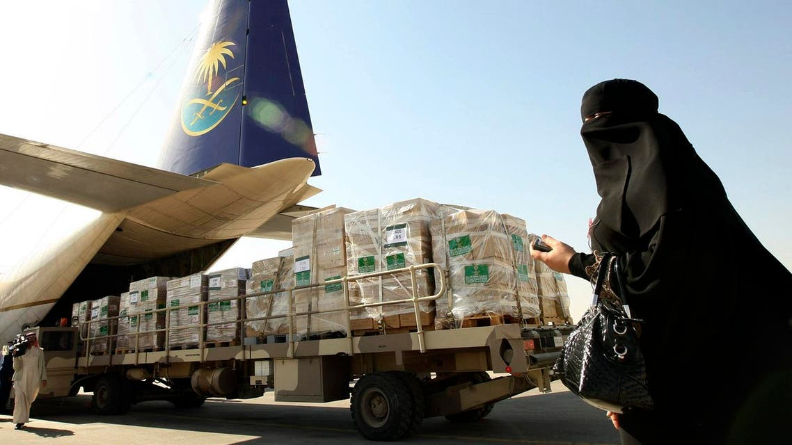 A woman walks by as emergency aid and goods are loaded onto a cargo plane bound for Gaza. (Reuters)