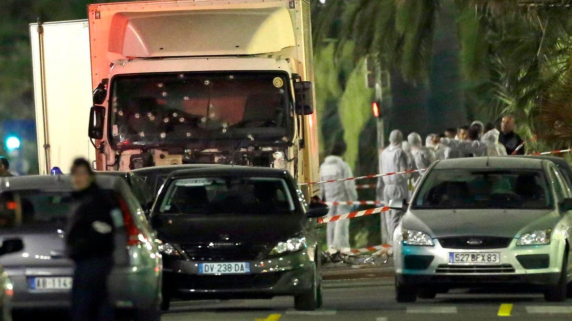 Forensic officers stand near a truck with its windscreen riddled with bullets, that plowed through a crowd of revelers who'd gathered to watch the fireworks in the French resort city of Nice, southern France, Friday, July 15, 2016. At least 80 people were killed before police killed the driver, authorities said. (AP Photo/Claude Paris)