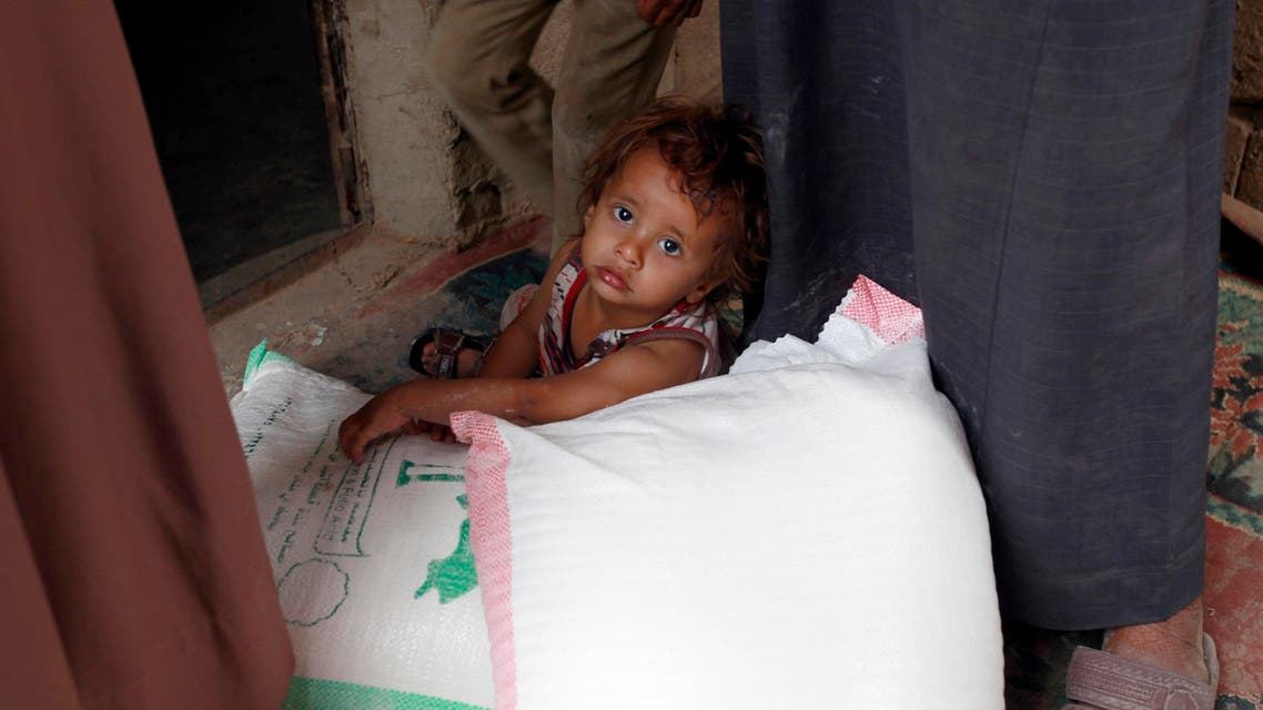 A Yemeni young child sits next to food rations that a local charity is distributing to families affected by the country's ongoing conflict during the fasting month of Ramadan on June 15, 2016 in an empoverished part of the capital Sanaa. Yemen's warring parties are struggling to seal a peace deal as mutual mistrust has overshadowed eight weeks of UN-brokered talks in Kuwait that have failed to achieve any major breakthrough. AFP