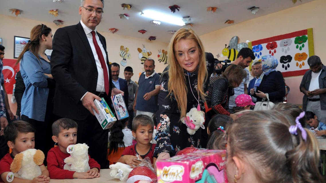 U.S. actress Lindsay Lohan gives presents to Syrian refugee children as she visits a Turkish government-run Syrian refugee camp in Nizip near Turkey's border with Syria, Saturday, Oct. 8, 2016. AP