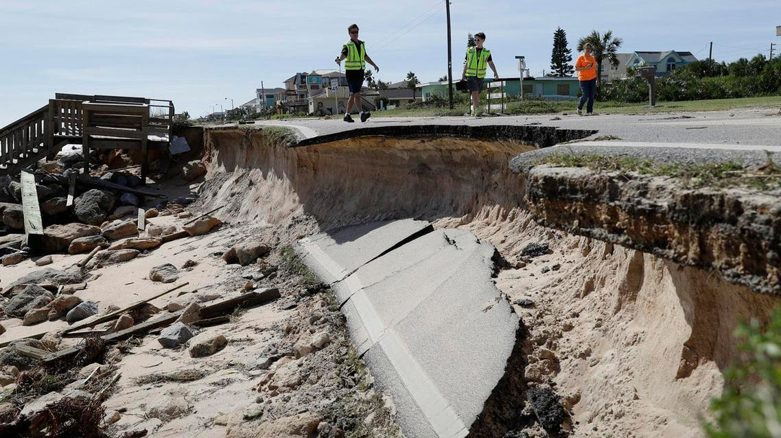 Officials photograph sections of highway A1A that were washed out by Hurricane Matthew, Saturday, Oct. 8, 2016, in Flagler Beach, Fla. The damage from Matthew caused beach erosion, washed out some roads and knocked out power for more than 1 million customers in several coastal counties. (AP Photo/Eric Gay)