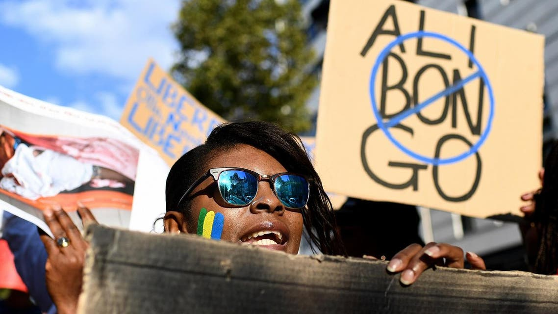 People hold a banner and photos during a demonstration of Gabonese associations in Marseille, southern France on September 24, 2016 to protest against the validation of reelection of Gabon's president Ali Bongo. (AFP)