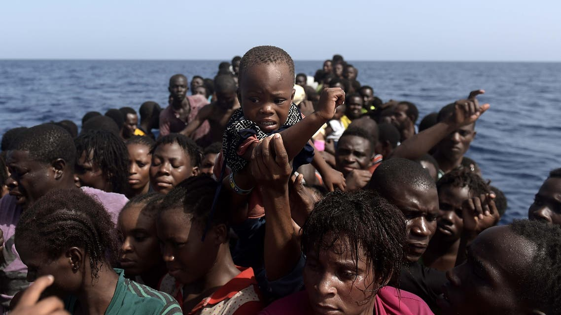 Migrants wait to be rescued by members of Proactiva Open Arms NGO in the Mediterranean Sea, some 12 nautical miles north of Libya, on October 4, 2016. At least 1,800 migrants were rescued off the Libyan coast, the Italian coastguard announced, adding that similar operations were underway around 15 other overloaded vessels. ARIS MESSINIS / AFP