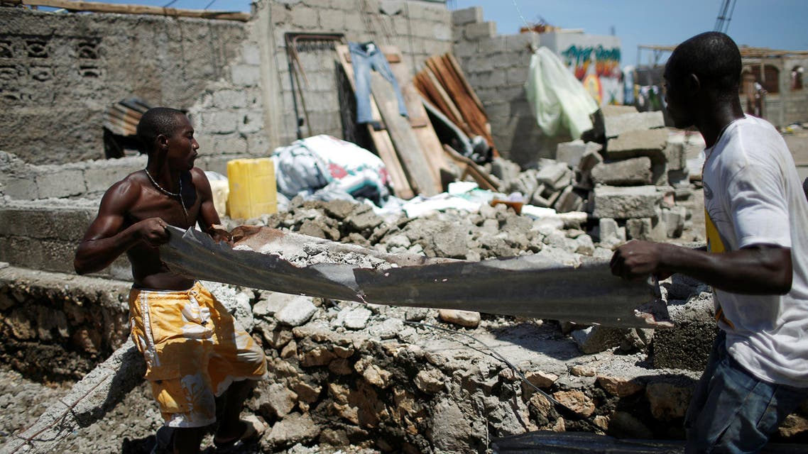 Men remove rubble on a metal sheet after Hurricane Matthew passes in Jeremie, Haiti, October 8, 2016. (Reuters)