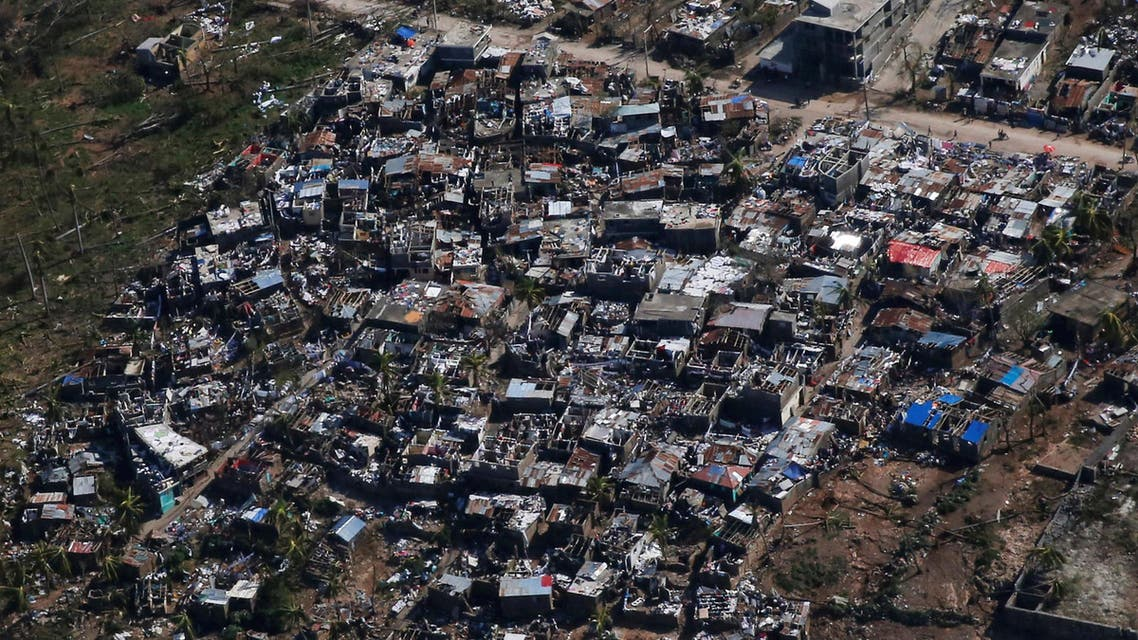 People walk down a street next to destroyed houses after Hurricane Matthew hit Jeremie, Haiti, October 7, 2016. (Reuters)