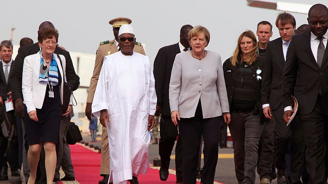 Malian President Ibrahim Boubacar Keita, center left, walk with German Chancellor Angela Merkel, center right, after her arrival at the airport in Bamako, Mali, Sunday, Oct. 9, 2016. German Chancellor Merkel is on a three day tour in Africa, visiting, Mali, Niger, and Ethiopia. (AP)