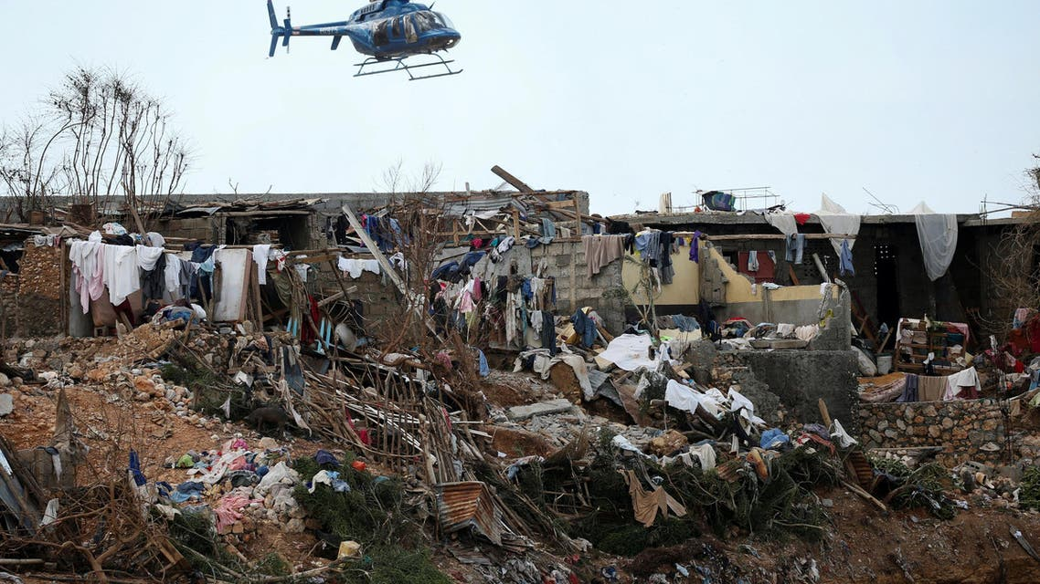 A helicopter flies over destroyed houses after Hurricane Matthew passes Jeremie, Haiti, October 7, 2016. (Reuters)