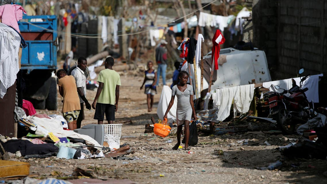 People walk down the street in front of destroyed houses after Hurricane Matthew passes Jeremie, Haiti, October 7, 2016. (Reuters)