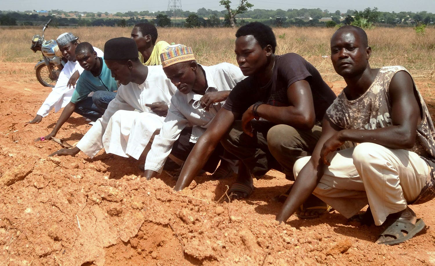 members of the Islamic Movement of Nigeria (IMN), a Shiite group, praying at a mass grave in the outskirts of northern Nigerian city of Kaduna. (AFP)