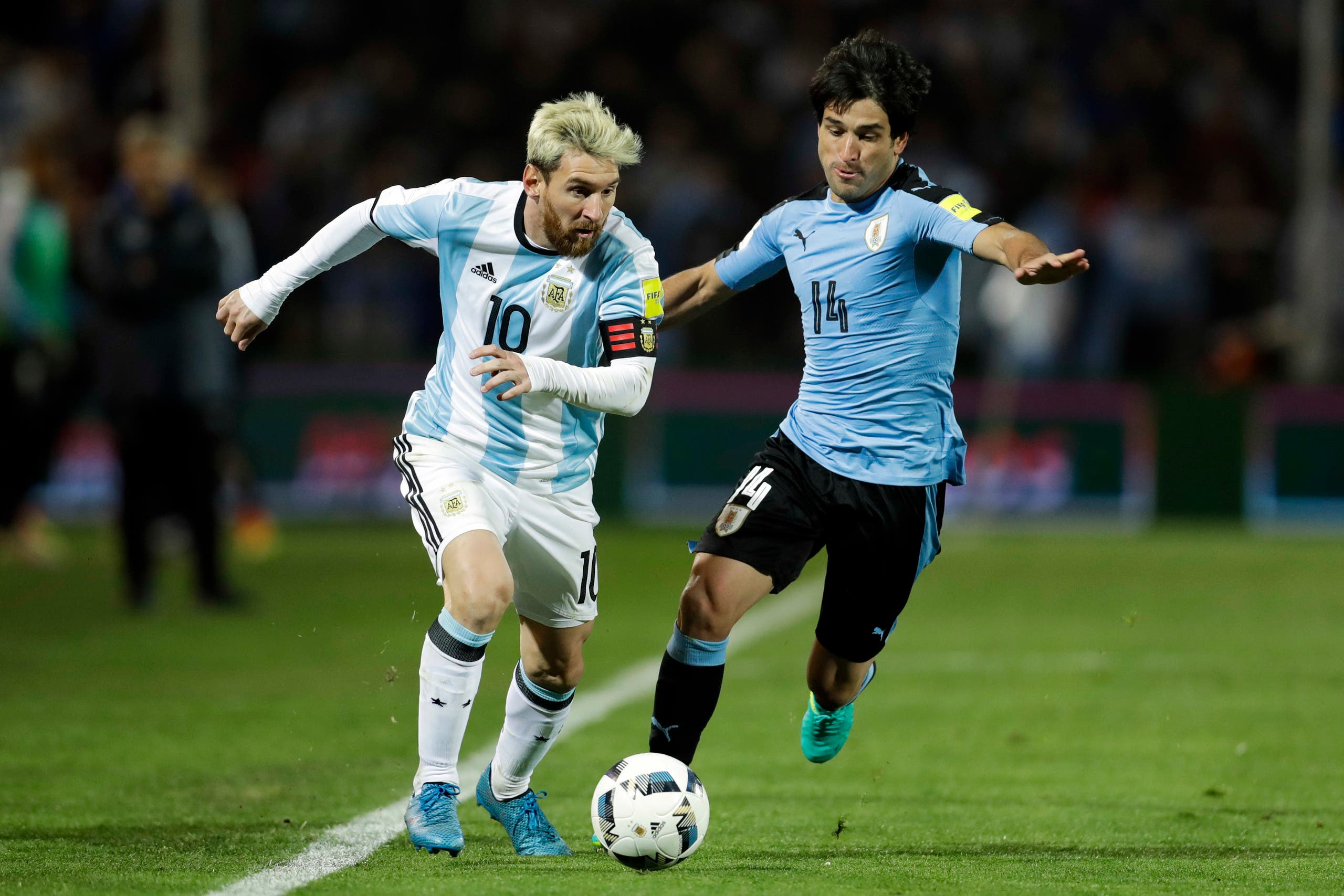 Argentina's Lionel Messi, left, vies for the ball with Uruguay's Nicolas Lodeiro during a 2018 World Cup qualifying soccer match in Mendoza, Argentina, Thursday, Sept. 1, 2016. (AP)