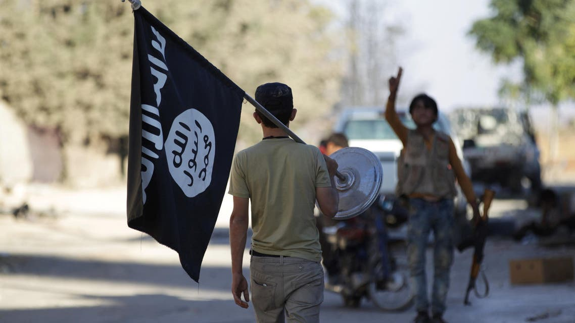 A rebel fighter takes away a flag that belonged to Islamic State militants in Akhtarin village, after rebel fighters advanced in the area, in northern Aleppo Governorate, Syria, October 7, 2016. reuters