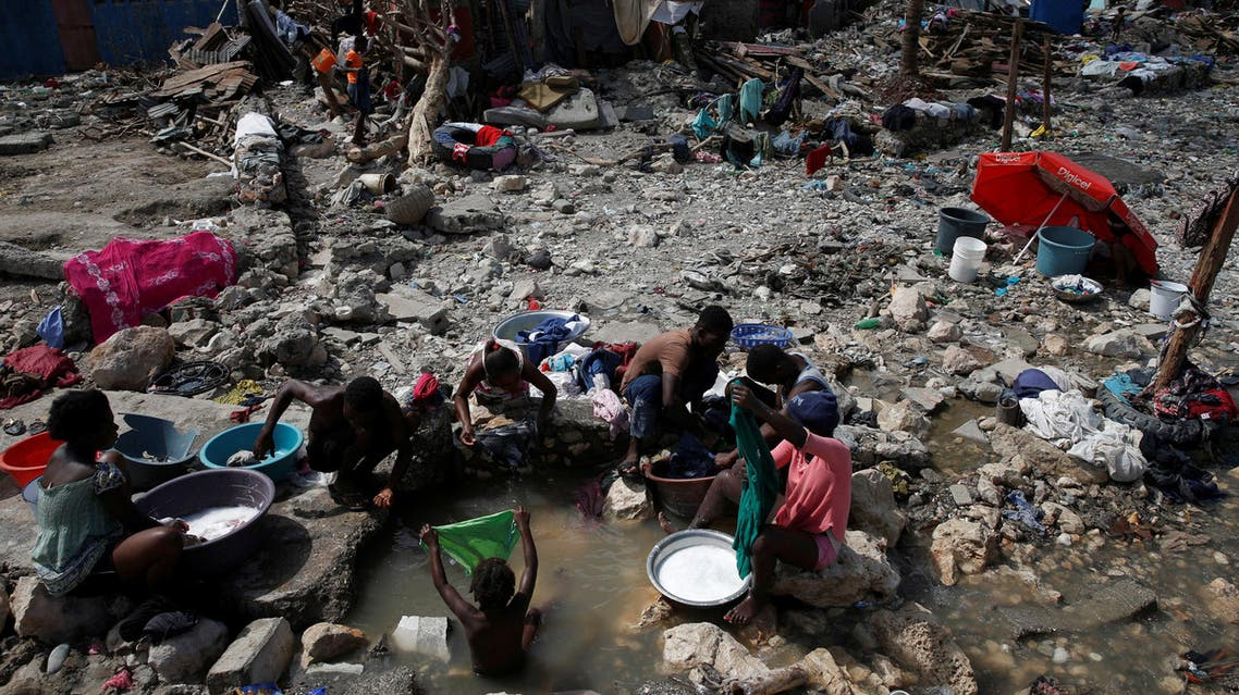 People wash their clothes on a beach near destroyed houses after Hurricane Matthew hit Jeremie, Haiti, October 10, 2016. (Reuters)