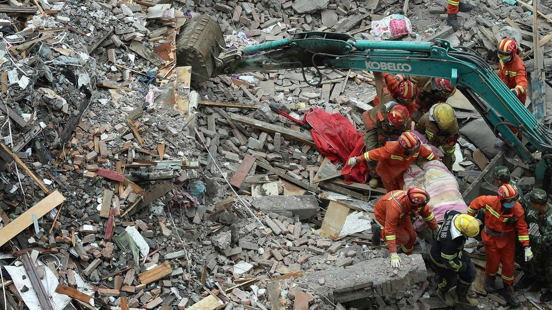 Rescuers carry a victim away from the site of a collapsed residential buildings in Wenzhou city in east China's Zhejiang province  (Photo: Chen Jianli/Xinhua via AP)