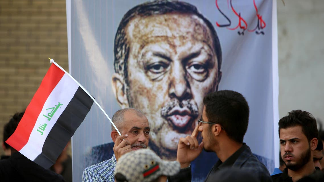 Iraqis, one with a national flag, stand in front of a banner bearing a portrait of Turkish President Recep Tayyip Erdogan during a demonstration to demand the withdrawal of the Turkish troops from the Bashiqa camp, located in the Mosul province, on October 8, 2016 outside the Turkish Embassy in Baghdad. Turkey said on October 6, 2016 that its troops will remain in Iraq despite Baghdad's growing anger ahead of a planned operation to retake the Iraqi city of Mosul from Islamic State group jihadists. Turkey has an estimated 2,000 troops in Iraq -- around 500 of them in the Bashiqa camp in northern Iraq training Iraqi fighters who hope to participate in the battle to recapture Mosul, according to Turkish media. (AFP)
