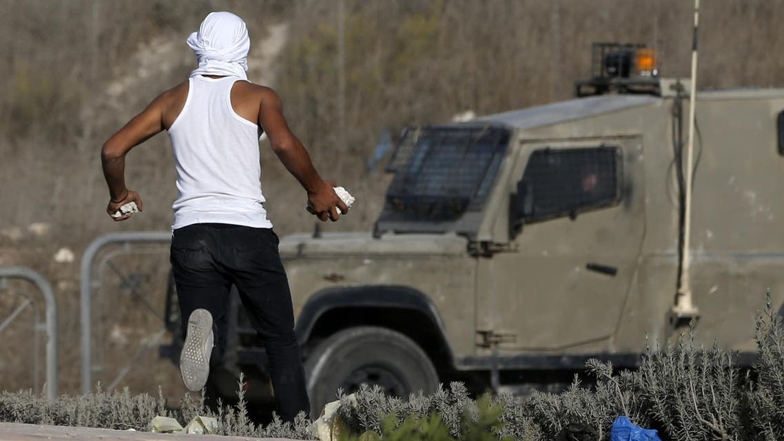 A masked Palestinian youth prepares to throw stones towards Israeli security forces during clashes in the West Bank town of al-Ram, north of Jerusalem, on October 9, 2016. (AFP)