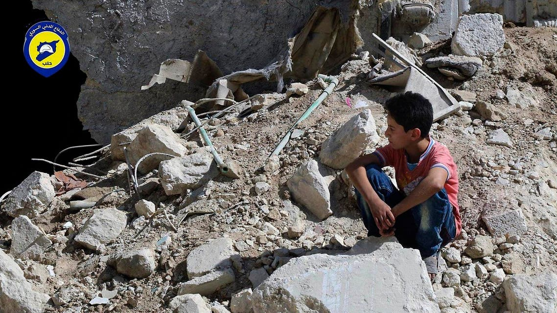 In this picture taken, Tuesday, Oct. 11, 2016, provided by the Syrian Civil Defense group known as the White Helmets, a boy sits amongst rubble in rebel-held eastern Aleppo, Syria (File Photo: Syrian Civil Defense- White Helmets via AP)