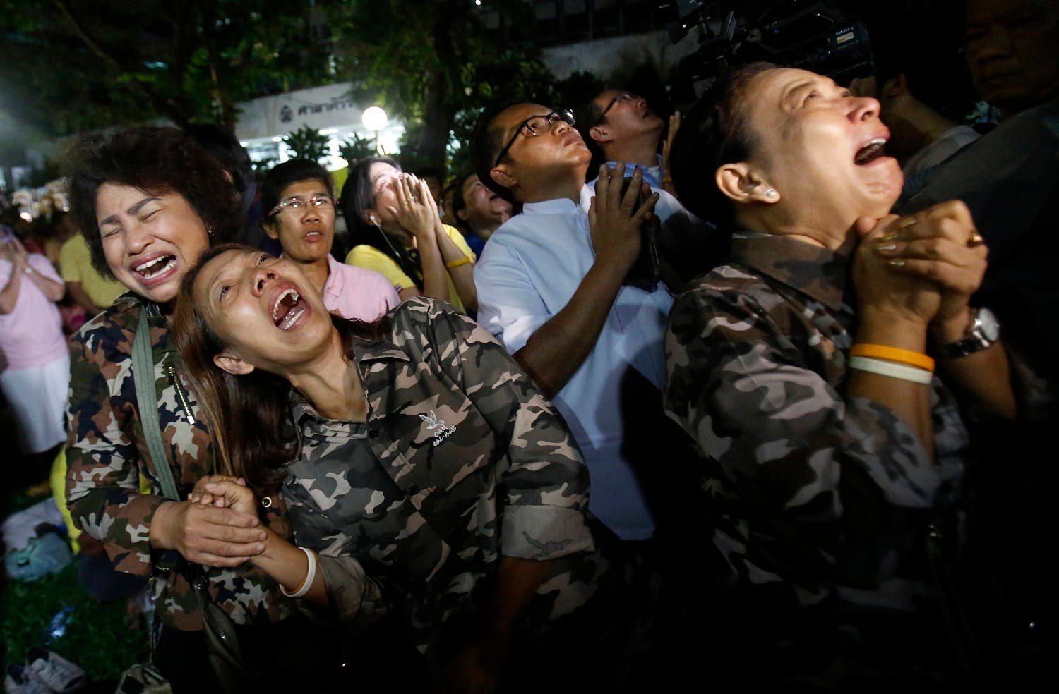 Thai people cry after Royal Palace's announcement outside Siriraj Hospital where King Bhumibol Adulyadej was being treated, in Bangkok, Thailand, Thursday, Oct. 13, 2016 (Photo: AP /Sakchai Lalit)