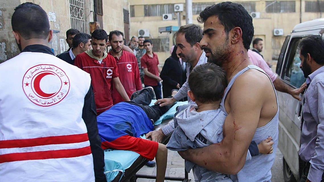 A Syrian man carries a child as they await treatment at a hospital in the regime-held part of Aleppo. (AFP)