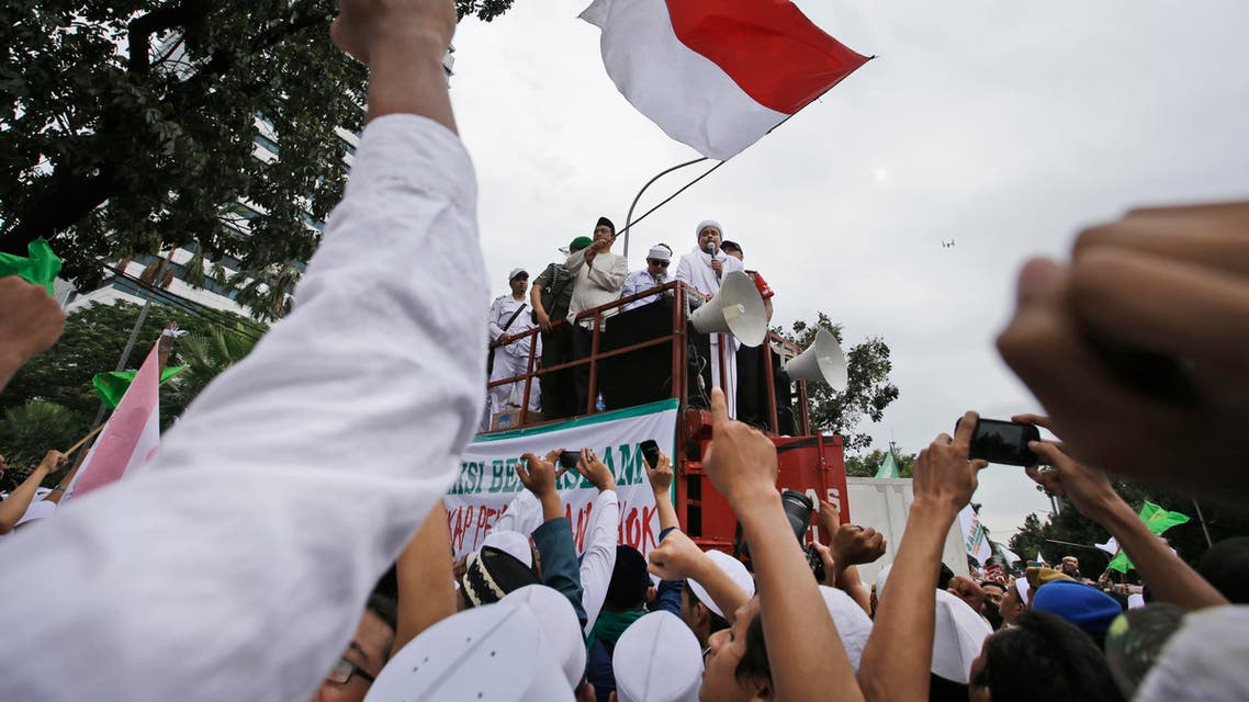 Muslim protesters raise their fists as the leader of Islamic Defenders Front, Rizieq Shihab, center, delivers his speech during a protest against Jakarta's ethic Chinese and Christian Governor Basuki Tjahaja Purnama, popularly known as Ahok, outside the City Hall in Jakarta, Indonesia, on Friday, Oct. 14, 2016. AP