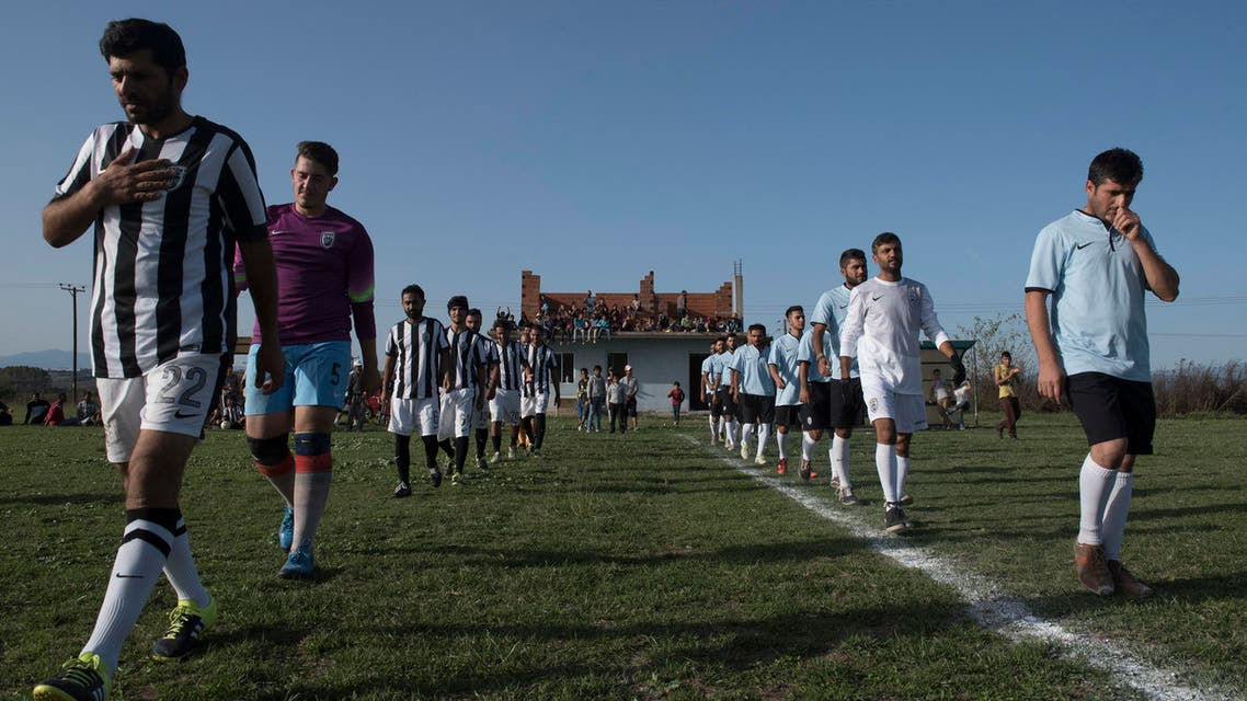 Players of Herso refugee camp team left and Nea Kavala refugee camp team walk on the field before the start their soccer match, in the village of Nea Kavala, northern Greece. AP