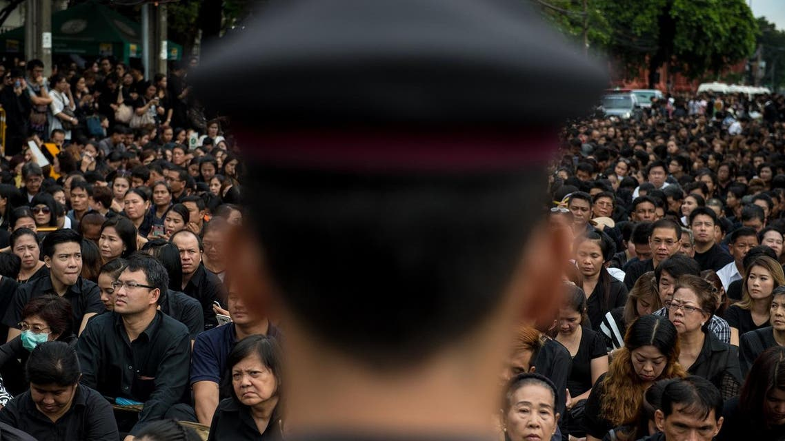 A large crowd clad in black who came to pray for the late Thai King Bhumibol Adulyadej is watched by a Thai policeman in front of the Grand Palace in Bangkok on October 16, 2016 AFP