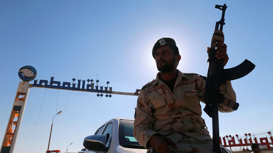 A member of Libyan forces loyal to eastern commander Khalifa Haftar holds a weapon as he sits on a car in front of the gate at Zueitina oil terminal in Zueitina, west of Benghazi, Libya September 14, 2016. reuters