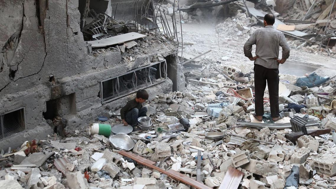 A Syrian boy collects items amidst the rubble of destroyed buildings on October 3, 2016. AFP