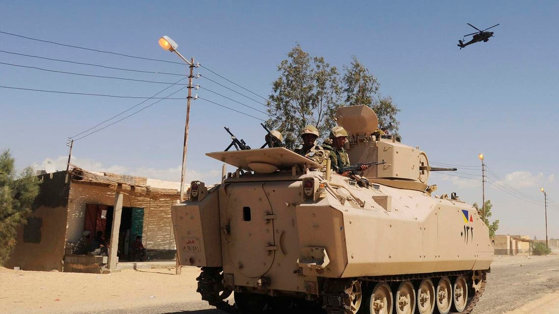In this May 12, 2013 file photo, Egyptian Army soldiers patrol in an armored vehicle backed by a helicopter gunship during a sweep through villages in Sheikh Zuweyid, north Sinai, Egypt. (AP)
