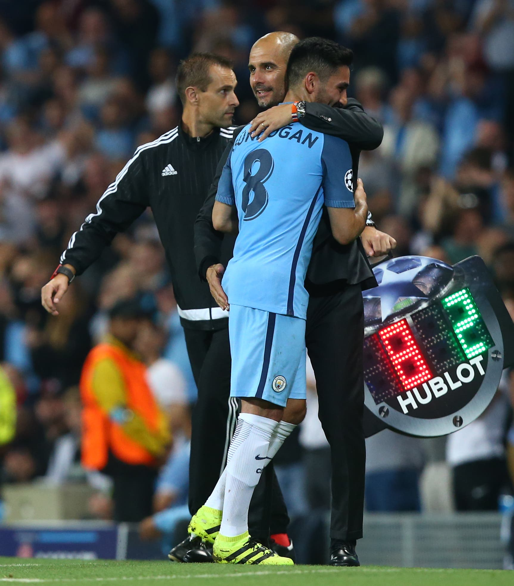 Manchester City's manager Pep Guardiola, centre, hugs his player Manchester City's Ilkay Gundogan as he is substituted during the Champions League group C soccer match at the Etihad Stadium between Manchester City and Borussia Moenchengladbach in Manchester, England, Wednesday, Sept. 14, 2016. The match was rearranged from Tuesday due to adverse weather conditions in Manchester. (AP