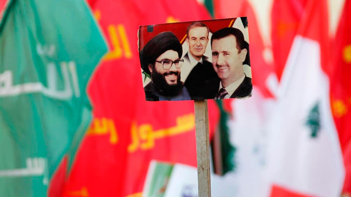Supporters of Lebanon's Hezbollah leader Sayyed Hassan Nasrallah wave flags and a picture depicting (L-R) Lebanon's Hezbollah leader Sayyed Hassan Nasrallah, Syria's late President Hafez al-Assad, father of current President Bashar al-Assad. (Reuters)