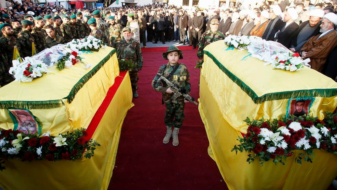 The son of Lebanon's Hezbollah soldier Abbas Hijazi, who died in an airstrike in Quneitra, carries a toy weapon as he stands between his father's (R) and grandfather's (L) coffins. (Reuters)