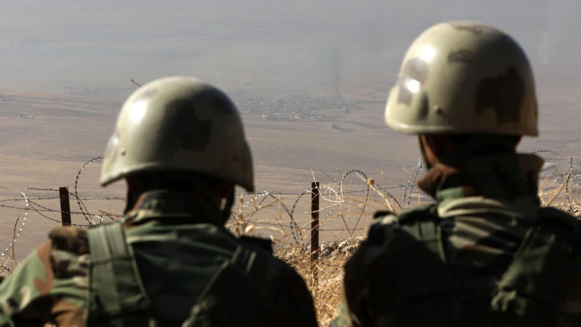 A picture taken from the top of Mount Zardak, about 25 kilometres east of Mosul, shows Iraqi Kurdish Peshmerga fighters watching smoke billowing during an operation against Islamic State (IS) group jihadists to retake the main hub of Mosul, on October 17, 2016. Thousands of Iraq's Kurdish peshmerga forces advanced on jihadist-held villages east of Mosul as part of a broad operation to retake the city from the Islamic State group. SAFIN HAMED / AFP
