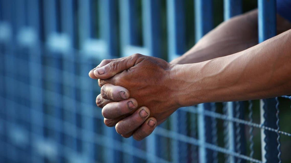 prison bars hands shutterstock