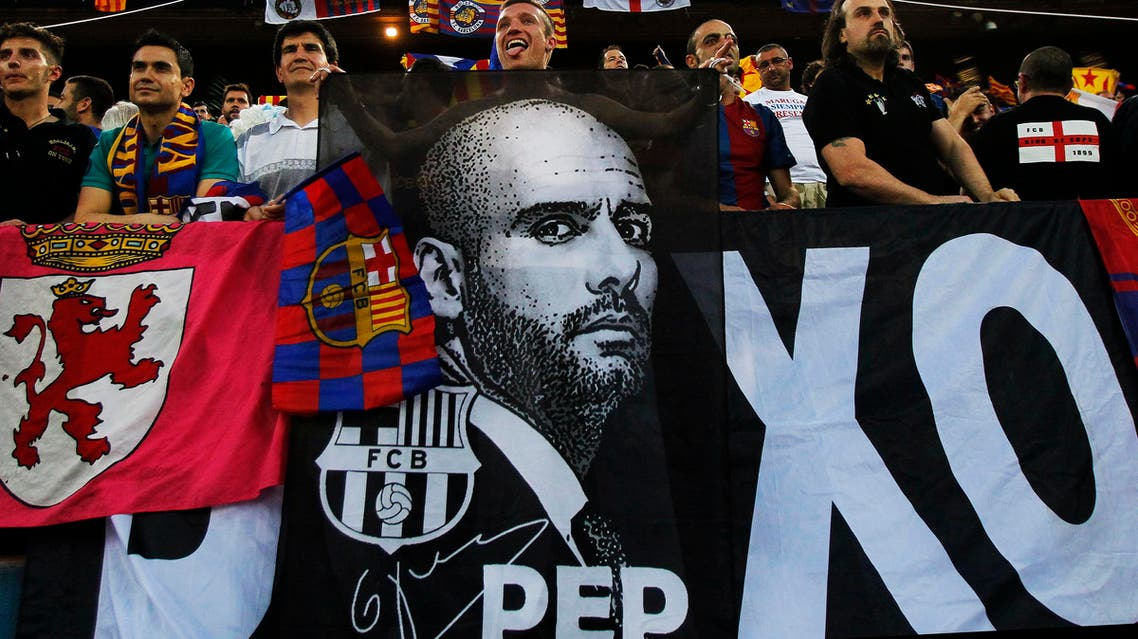 FC Barcelona's fans hold a banner of the team's coach Josep Guardiola and team flags during Copa del Rey soccer match final against Athletic Bilbao in Madrid, Spain, Friday, May 25, 2012. (AP