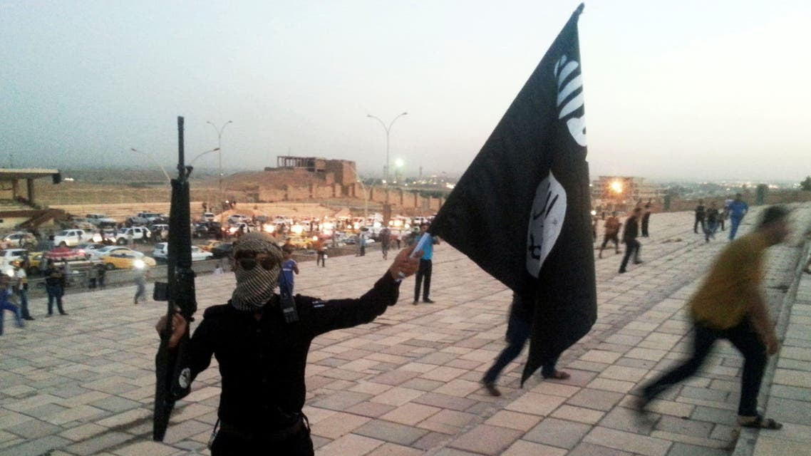A fighter of the Islamic State of Iraq and the Levant (ISIL) holds an ISIL flag and a weapon on a street in the city of Mosul June 23, 2014. (AP)