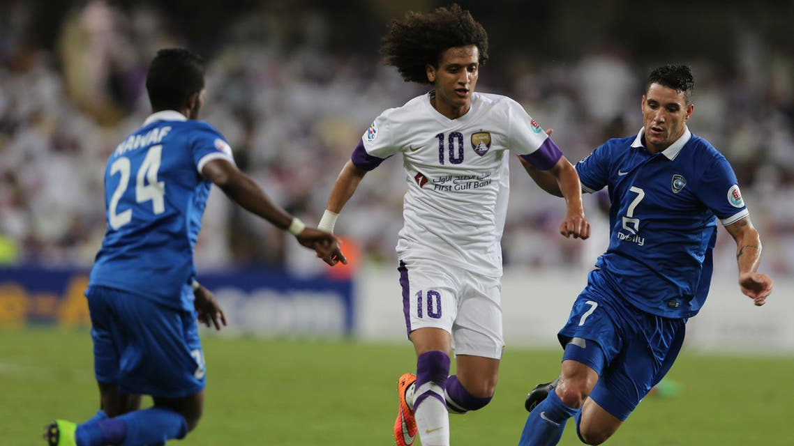 Omar Abdulrahman of UAE's Al Ain, center, battles for the ball with Neves Augusto Thiago of Saudi Arabia's Al Hilal, during a semifinal match of AFC Champions League in Al Ain, United Arab Emirates, Tuesday, Sept. 30, 2014. (AP