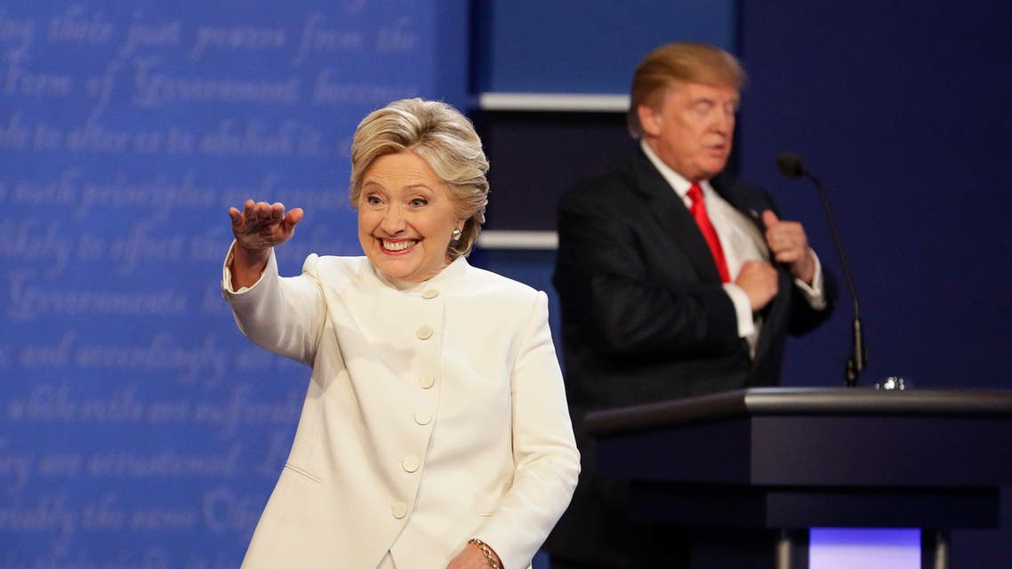 Democratic presidential nominee Hillary Clinton waves to the audience as Republican presidential nominee Donald Trump puts away his notes after the third presidential debate at UNLV in Las Vegas, Wednesday, Oct. 19, 2016. (AP
