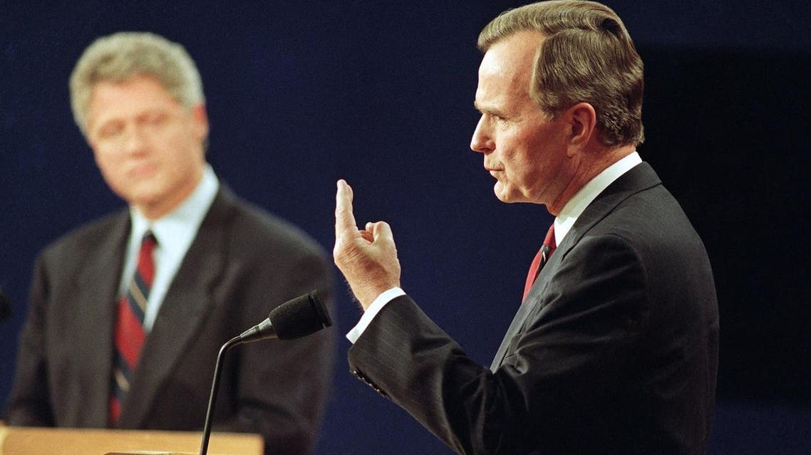 This photo from Oct. 12, 1992 shows Democratic presidential candidate Bill Clinton looking on at left, President George Bush speaks during the first presidential debate in St. Louis, Mo. (File Photo: AP/Bill Waugh)