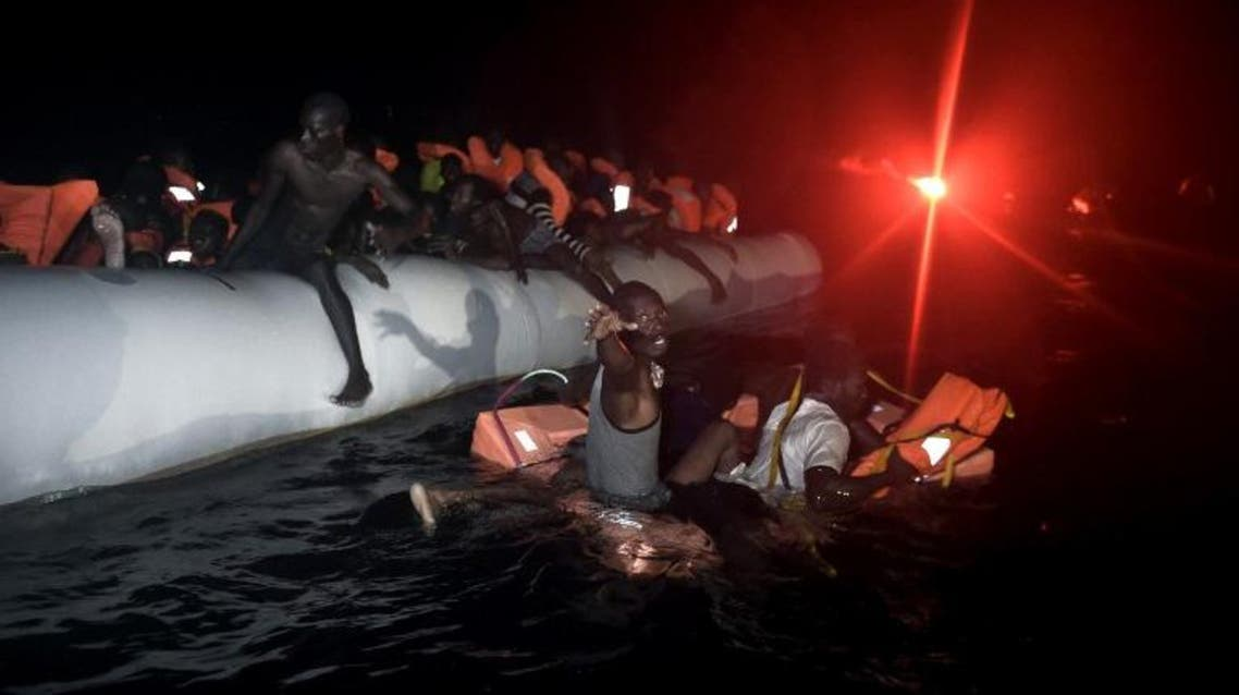 Migrants and refugees wait to be rescued from their sinking rubber boat some eight nautical miles off Libya's Mediterranean coastline on October 12, 2016. AFP