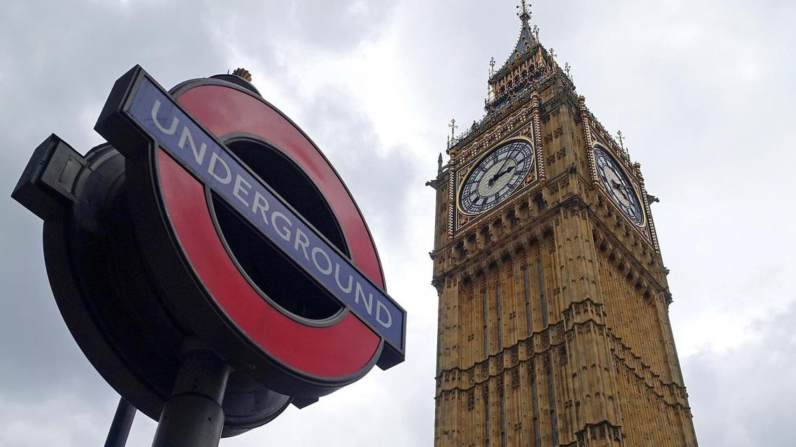 In this May 20, 2015 photo, a sign for the London Underground system appears next to the Big Ben bell clock and Elizabeth Tower in London. (AP Photo/Ross D. Franklin)