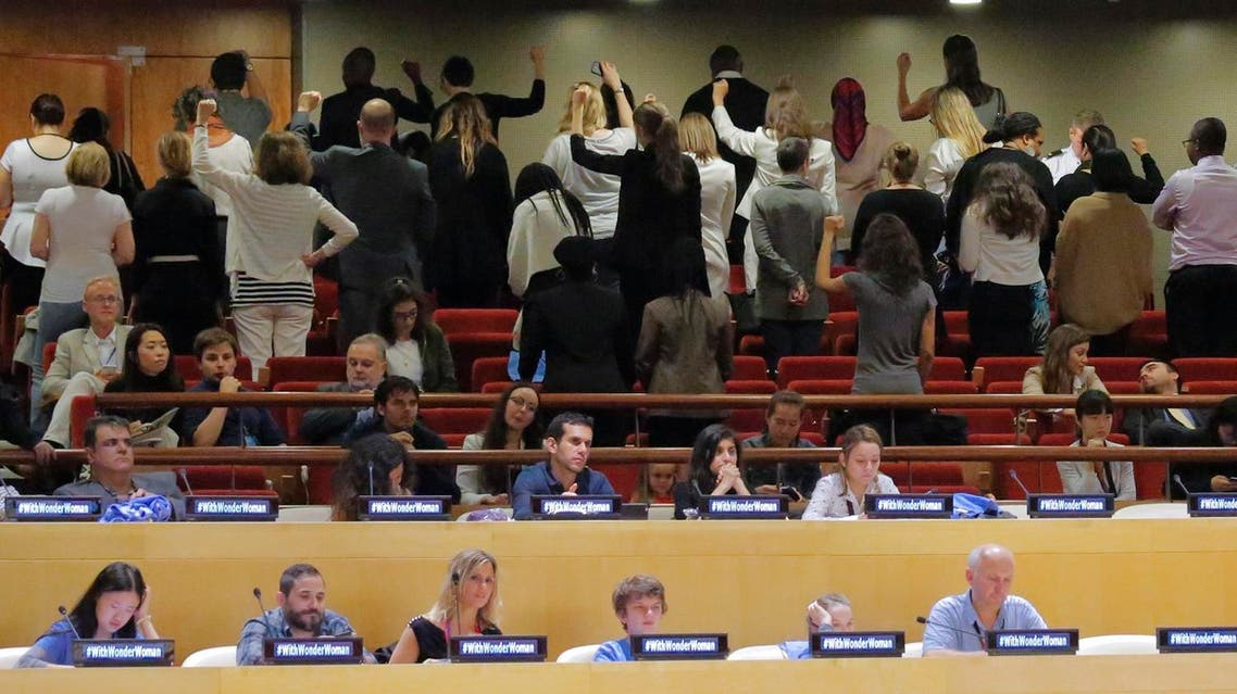 UN staff stand and turn their backs, top, in a silent protest (Photo: AP/Bebeto Matthews)